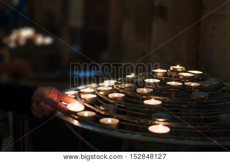 Woman lights candles church in  Notre Dame
