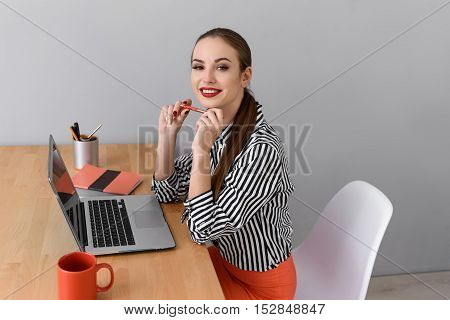 I like my job. Joyful young woman is sitting at desk and working with laptop. She is looking at camera and smiling