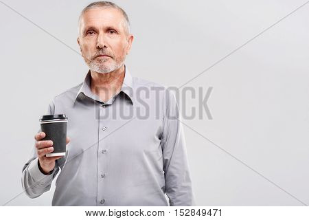 aged man holding a cup of coffee on gray background with copy space