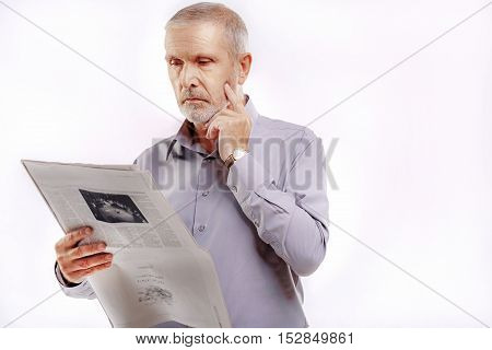 senior gentleman reading a newspaper on gray background