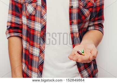 Pills, tablets and drugs heap in man hand on grey background
