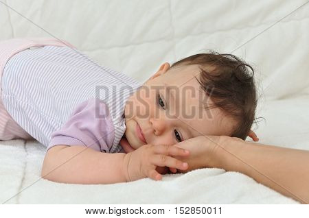 Tired baby girl resting her head on the palm of her mother