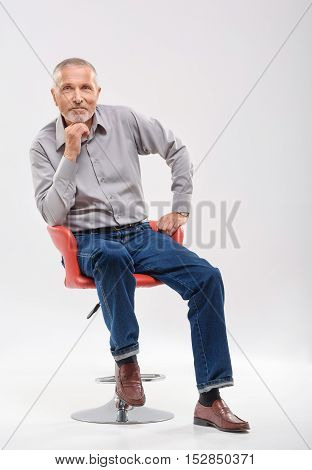 happy retired man sitting on a chair against gray background with copy space