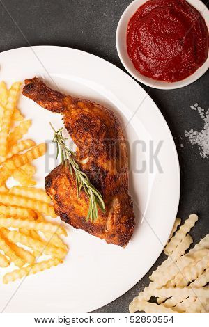 Fried Chicken leg with rosemary and french fries with sauce on a black chalkboard.