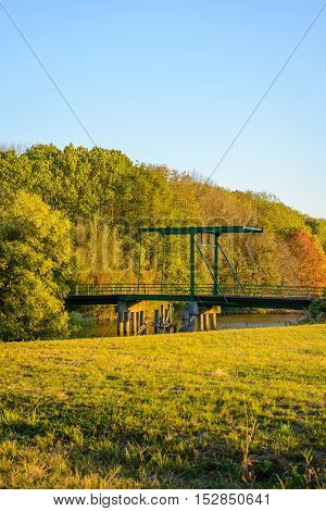 Green painted historic drawbridge from 1939 built across a creek in a Dutch nature reserve. It is a sunny day in the fall season.