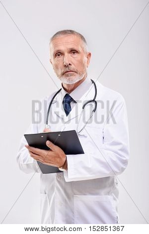 portrait of confident adult medical doctor on grey background