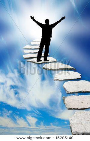 Silueta masculina en un camino de piedra que lleva al cielo
