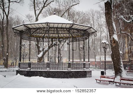 Arch in a city park covered with snow. Strong snow storm
