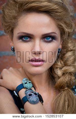 Portrait of young beautiful woman with light makeup and blue eyes touching her face. Wearing pearls bracelet and earrings.