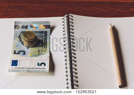 Blank notebook with pencil and euro money on wooden desk