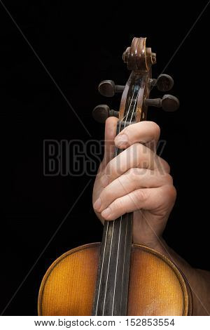 Close view of men's hand with old violin in a black background
