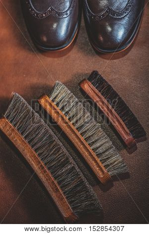 top view of an old different brushes on the brown table and brouges, footwear concept