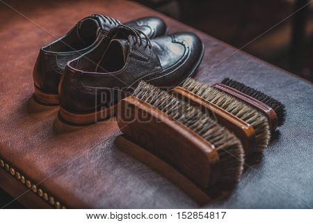 pair of footwear on the leather table next to tree brushes