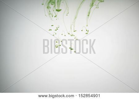 green ink poured in water, copy space for your info