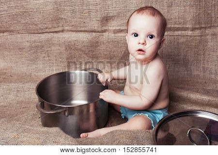 Child girl playing with cooking utensils she grabbed a pan