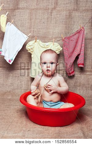 Little girl sits in a basin. Behind her hanged wash clothes