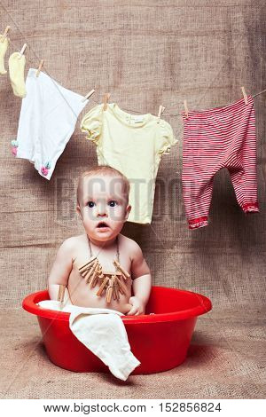 Baby girl sitting in a red a basin. Behind it on the clothesline drying things