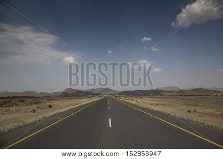 Empty road in remote Oman with mountains at the background