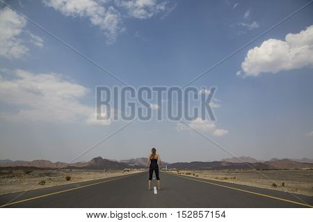 woman standing in a middle of an Empty road in remote Oman