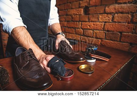 polisher standing at the desk with a boot and rag in his hands