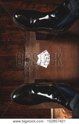 cards on a wooden surface with new black shoes