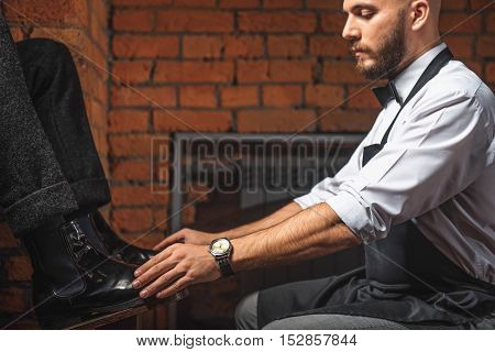 bald guy preparing for shoe shining and holding shoes of a customer indoors, close up