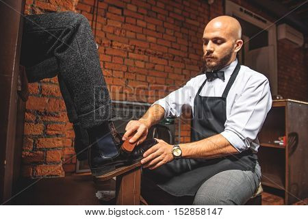 bald worker brushing brogues of a man who sitting in front of him