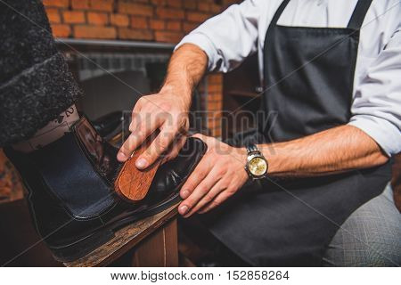 close up hands of a man in apron cleaning pair of boots with a brush