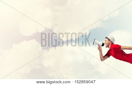 Young man shouting in megaphone with blue sky background