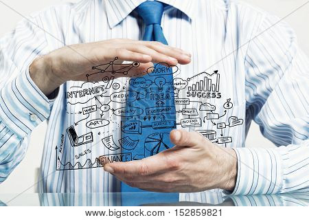 Businessman hand protecting business idea sketch with palms
