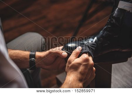man cleaning dirt from footwear with a wet rag, close up