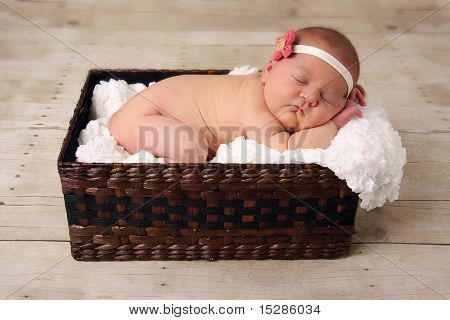 Newborn baby girl asleep in a wicker basket.