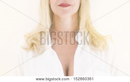 closeup of neck and chin of blond woman wearing a white shirt in bright soft light