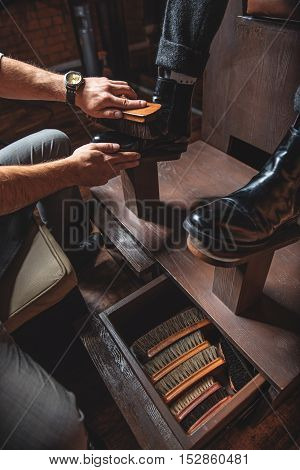 man gets his shoes polished by a craftsman using a vintage camel hair brushes on a wooden shoe platform