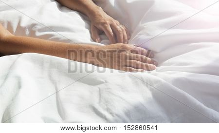 closeup of hands of woman on white bedsheets