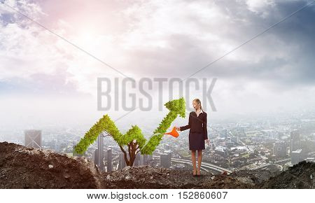 Young attractive businesswoman watering symbol chart plant in ground with can against the backdrop of the city