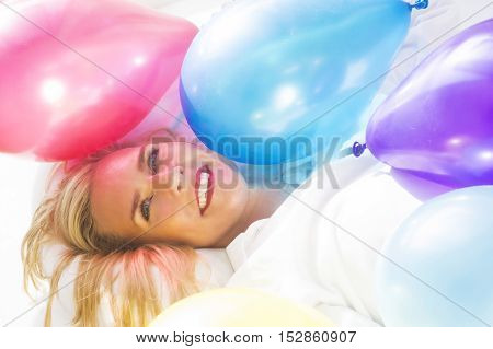 blond woman lying in bed with colorful balloons