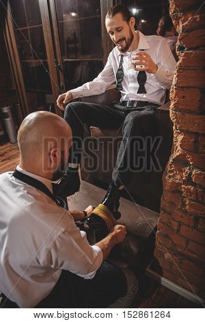 macho sitting in a wood chair and drinking and his footwear gets polished, close up