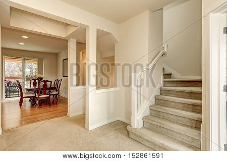 Beige Hallway With Staircase Leading Upstairs