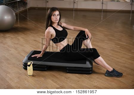 Young Happy Fit Woman Sitting On The Step Board At Gym