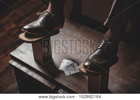leather elegant boots on the wooden shoe platform with playing cards, indoors