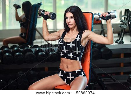 Woman Lifting Weights And Working On Her Shoulders At The Gym