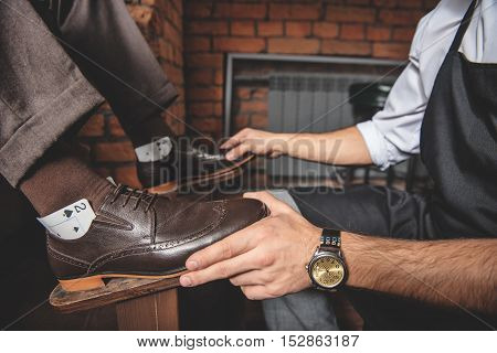 side view of shoes with playing cards on sides while worker adjusting a foot position