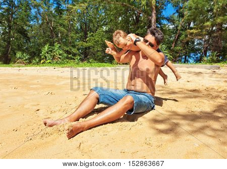 Father throws child into the air on a sandy tropical beach