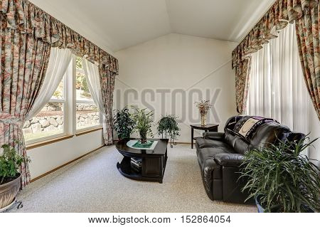 Cozy Sitting Area With Elegant Window Curtains And Vaulted Ceiling
