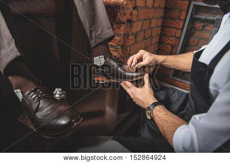 front view of brogues being polished by artisan indoors, close up