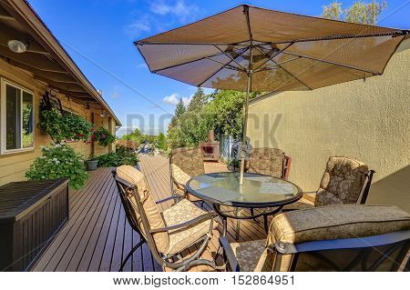 Patio Table Set With Opened Umbrella. Wooden Walkout Deck