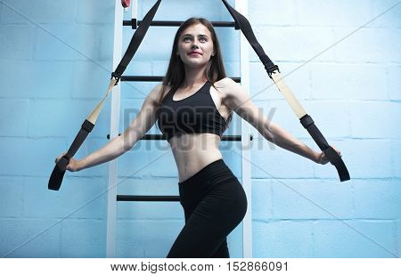 Young woman on elastic rope on  trx