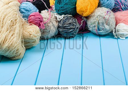 Many autumn colored yarn balls on the blue wooden background.