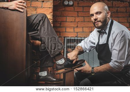 handsome bald man cleaning footwear and looking into the camera